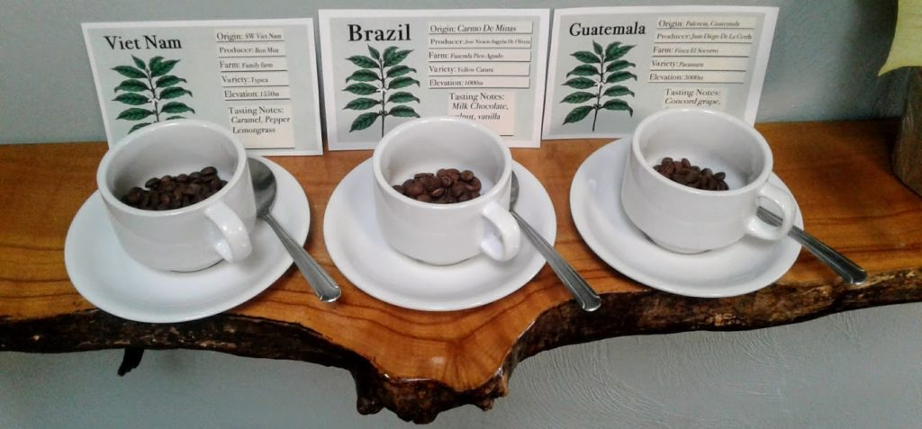 coffee beans in coffee cups in front of the label coffee varietal discriptions