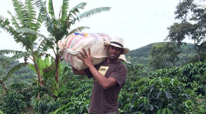 Okon carrying a bag of coffee beans on the farm
