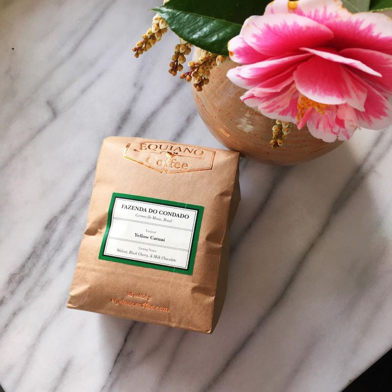 12 oz. bag of coffee on table next to a vase with pink flower