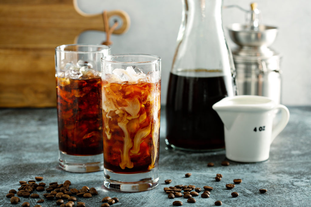 Refreshing cold brew iced coffee in tall glasses with cream